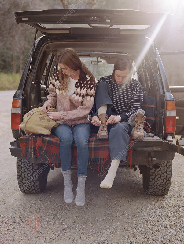 Young couple sitting, putting on boots