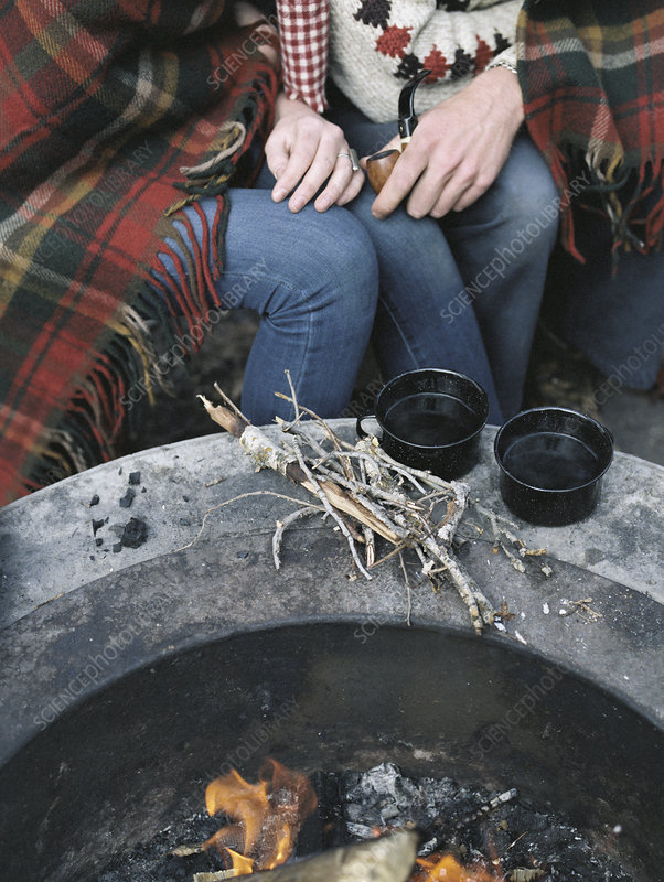 Detail of couple sitting by a fire pit