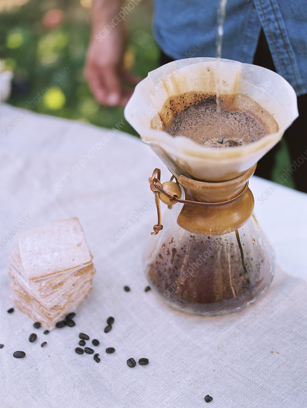 man standing at a table, making coffee