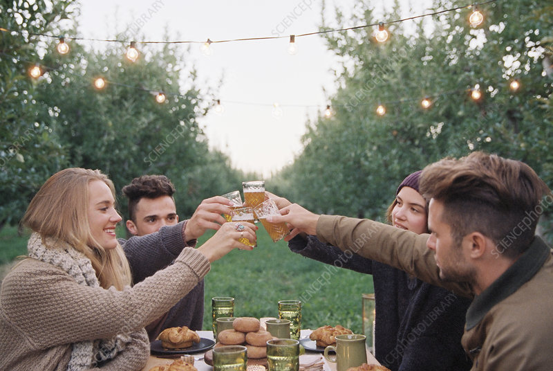 People toasting with a glass of cider