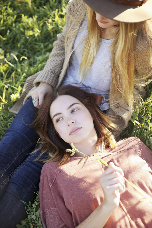 Two women lying in the grass in orchard