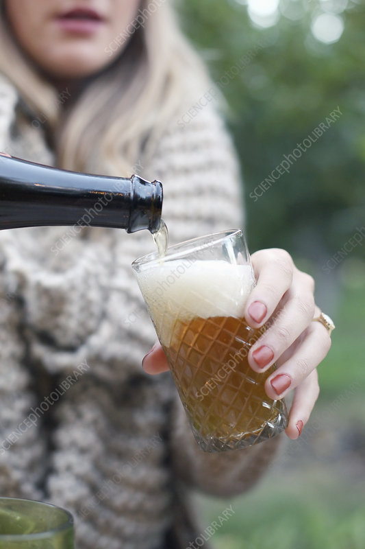 Woman pouring a glass of cider