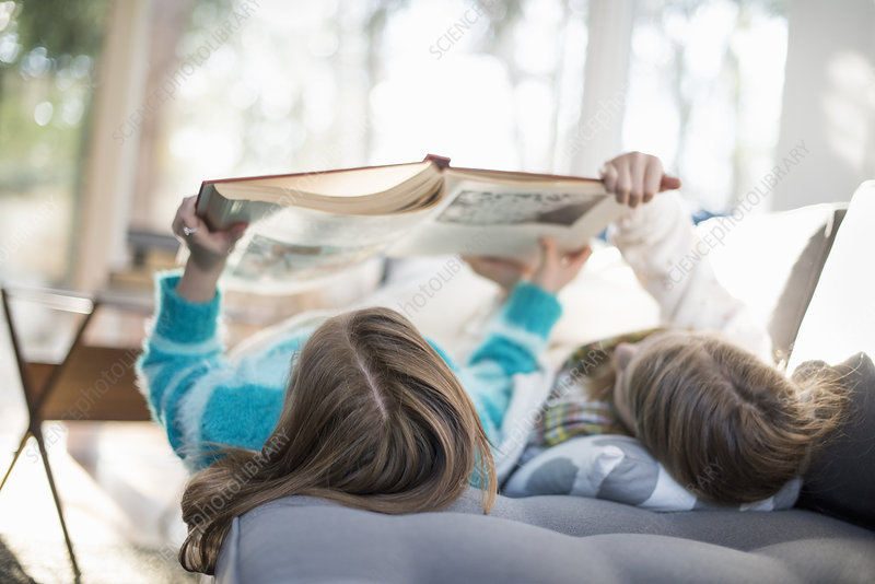 Two girls lying down reading a book