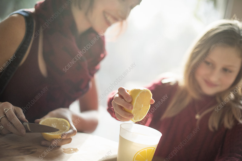 Girl squeezing lemon juice into a glass