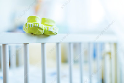Baby shoes on the edge of a cot