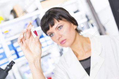 Lab assistant holding test tube