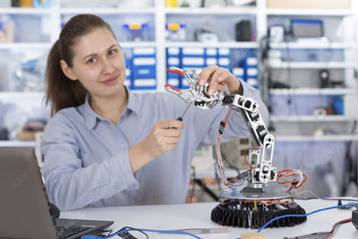 Student repairing robotic equipment