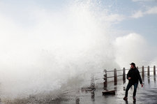 Man on sea front with crashing waves