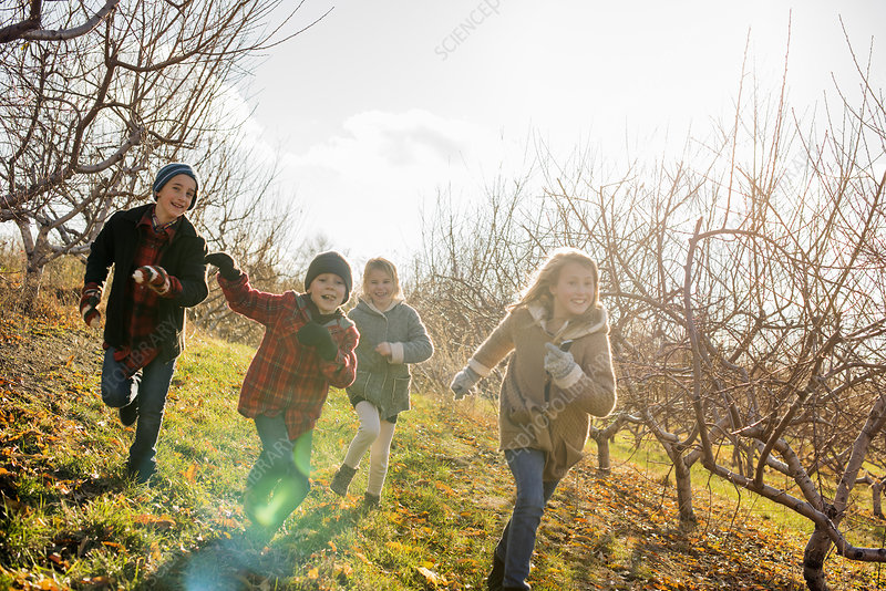Four children running outdoors in winter