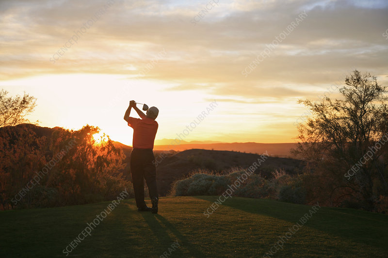 Golfer teeing off into the sunset