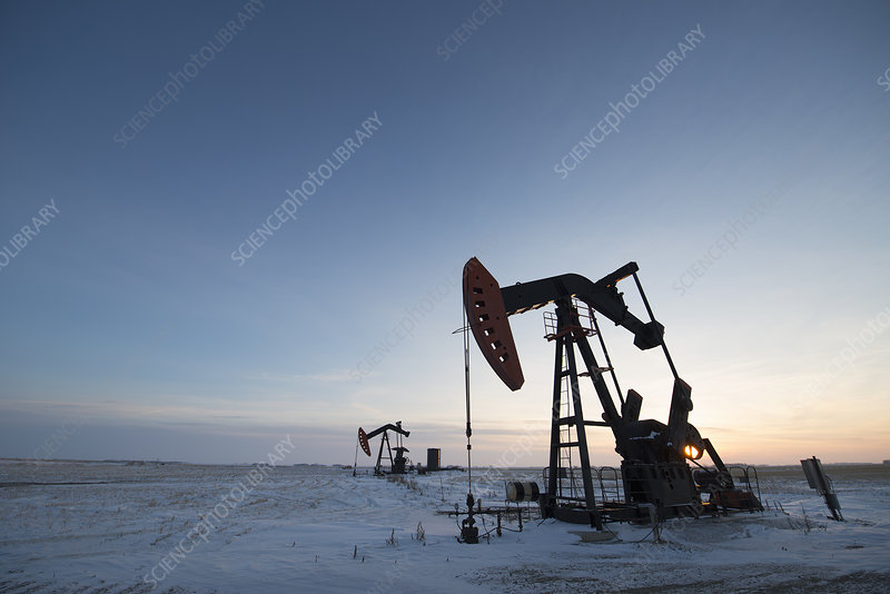 Oil drilling rig and pumpjack at sunset