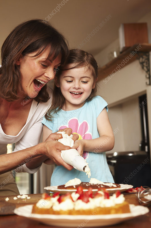 A mother and daughter icing a cake