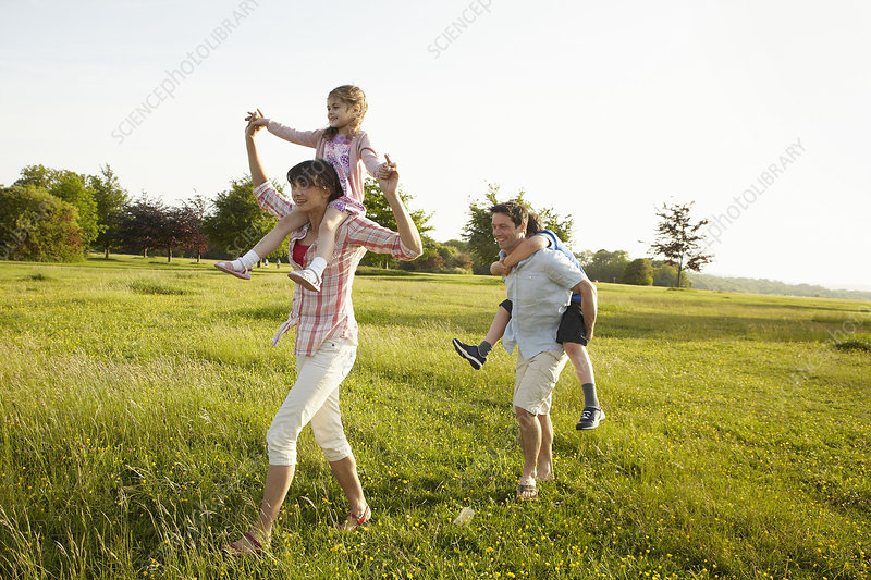 Two adults giving piggybacks to children