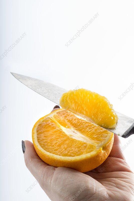Person slicing an orange