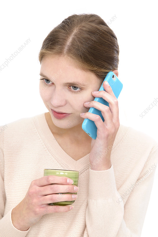 Woman on cell phone holding mug