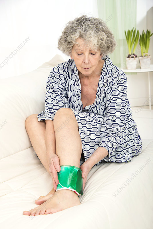 Woman with a cold compress on ankle