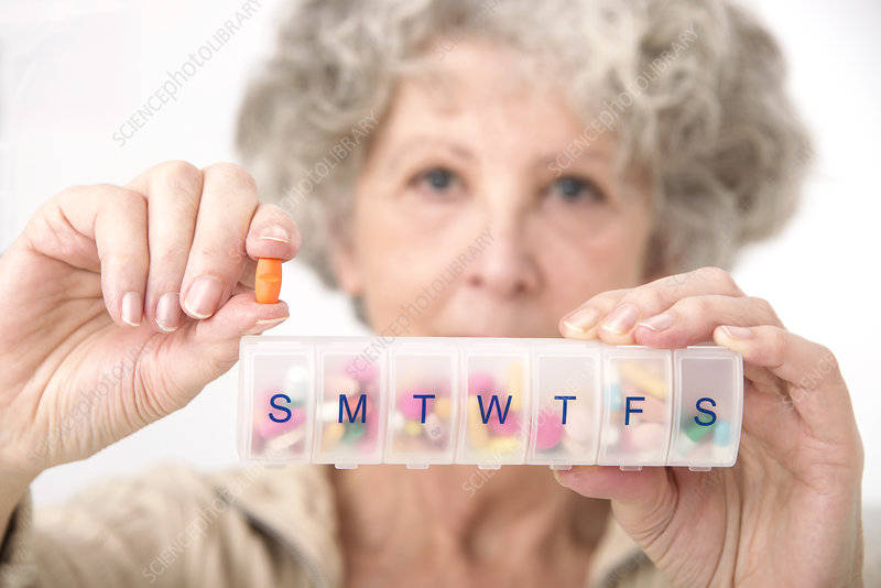 Woman holding pill and pill container