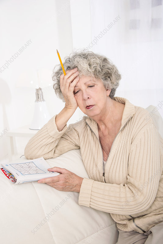 Woman holding puzzle book with hand on h