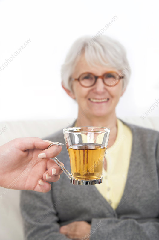 Woman with a hand holding glass of tea