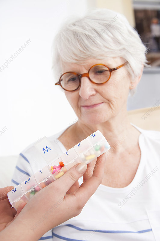 Woman looking at pill container