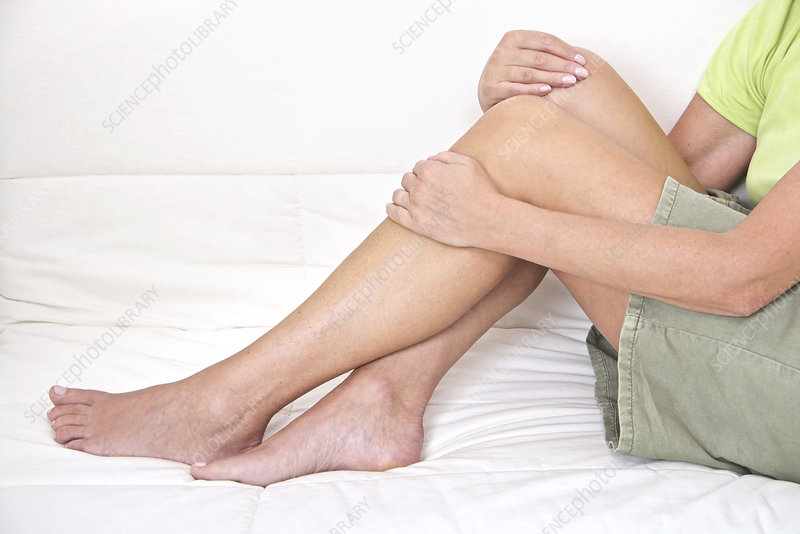 Mature woman holding legs
