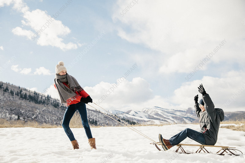 Girl pulling her brother on a sledge