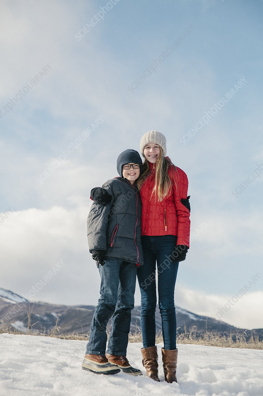 A brother and sister standing in snow