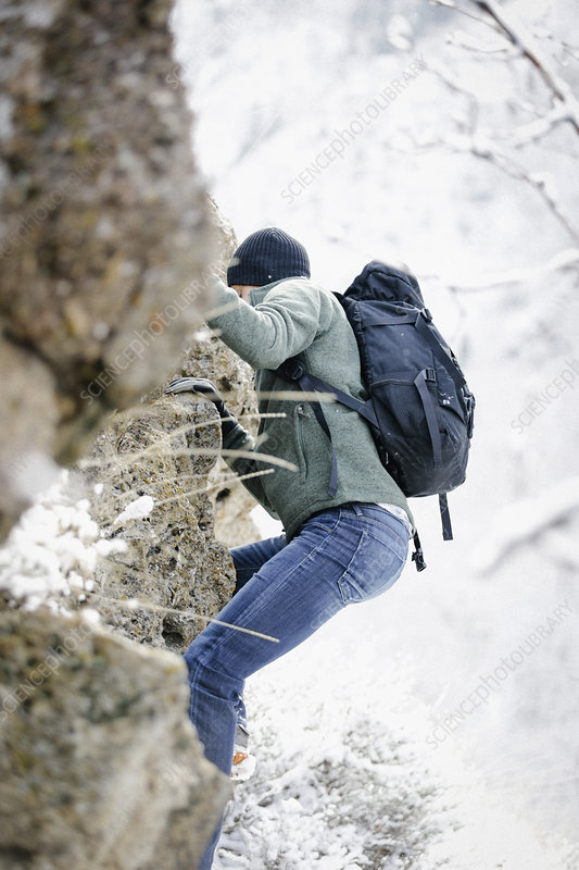A man climbing up a rocky cliff face