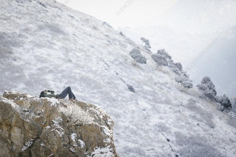 A man lying on a rock outcrop