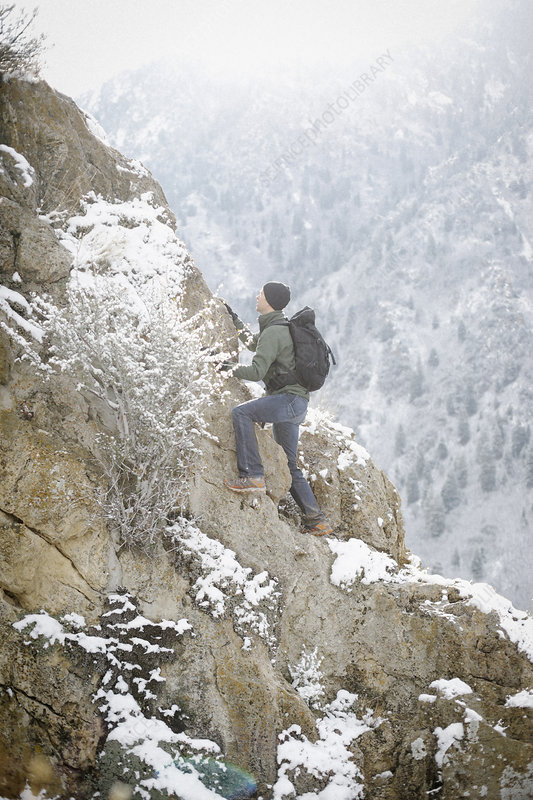 A man in the mountains climbing a cliff