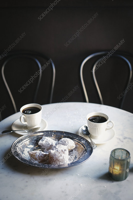 Two cups of coffee and a tray of pastries