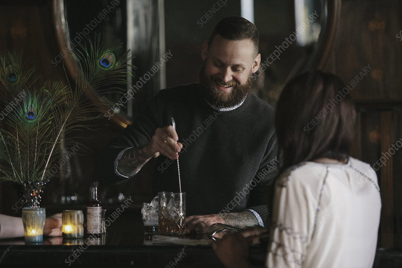 A woman and a bartender talking