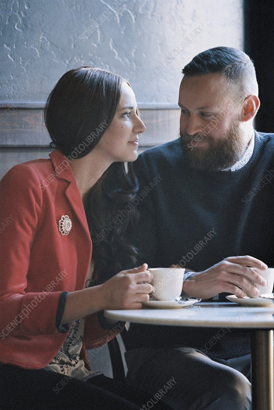 A couple seated at a cafe table