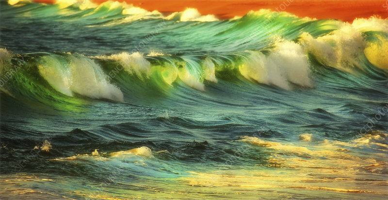 Waves and surf on a beach at sunset