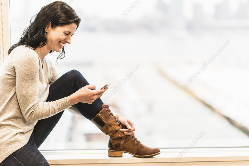A woman seated using her smart phone
