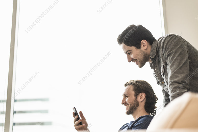 Two business men looking at a smart phone