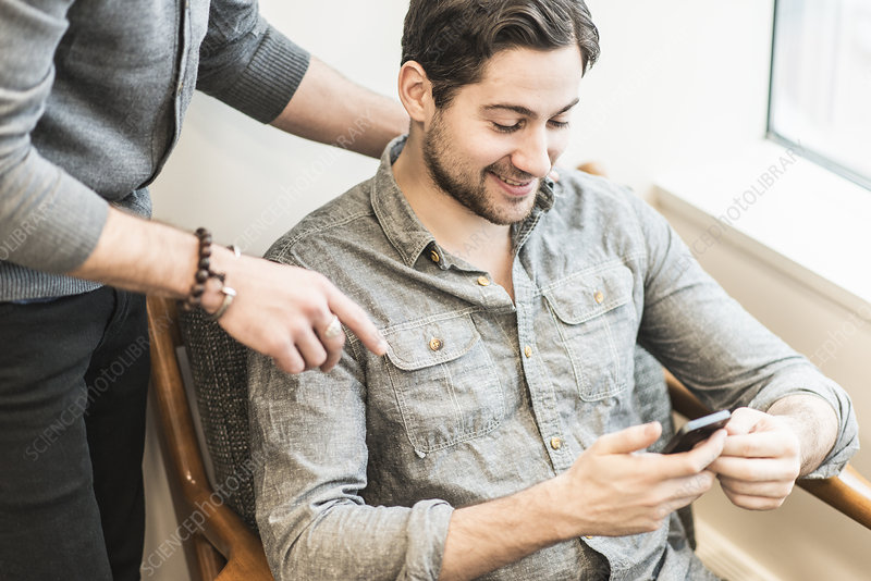 A man seated checking his smart phone