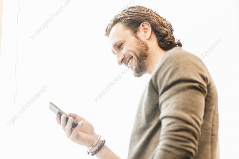 A bearded man checking his phone