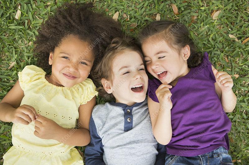 Three children lying on their backs