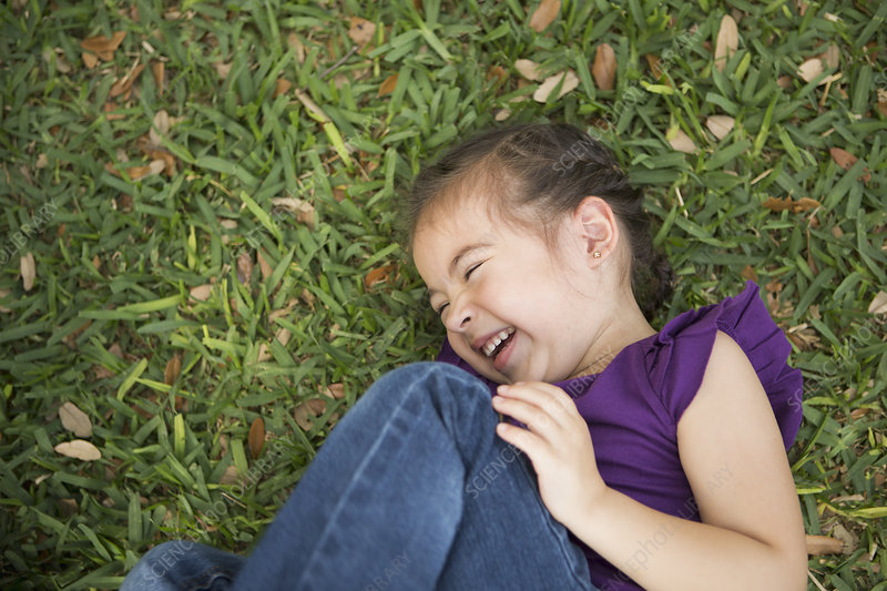 A girl lying on her side laughing