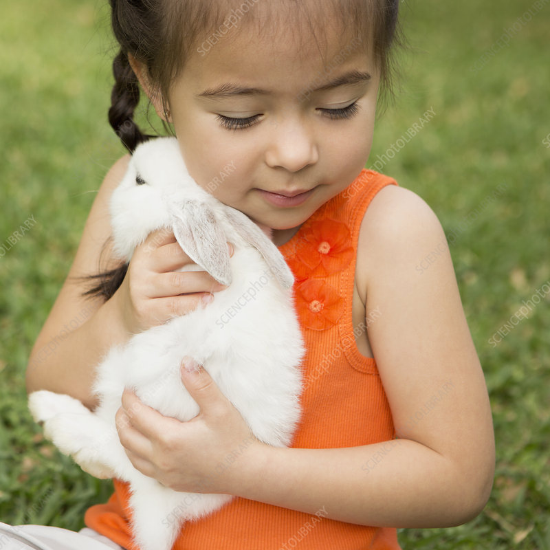 A child holding a large white rabbit
