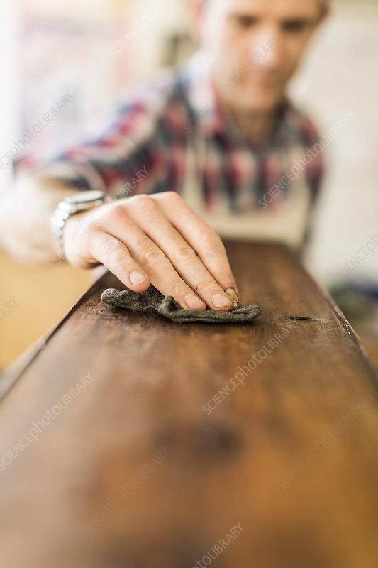 Antique furniture restorer polishing wood