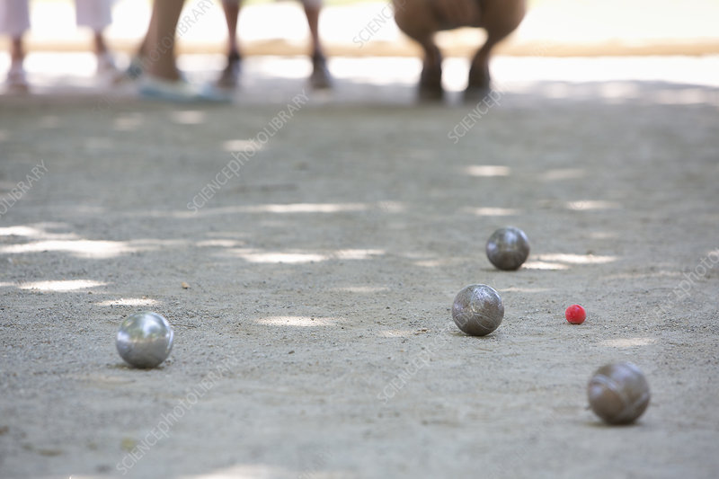 A boules game in progress in the shade