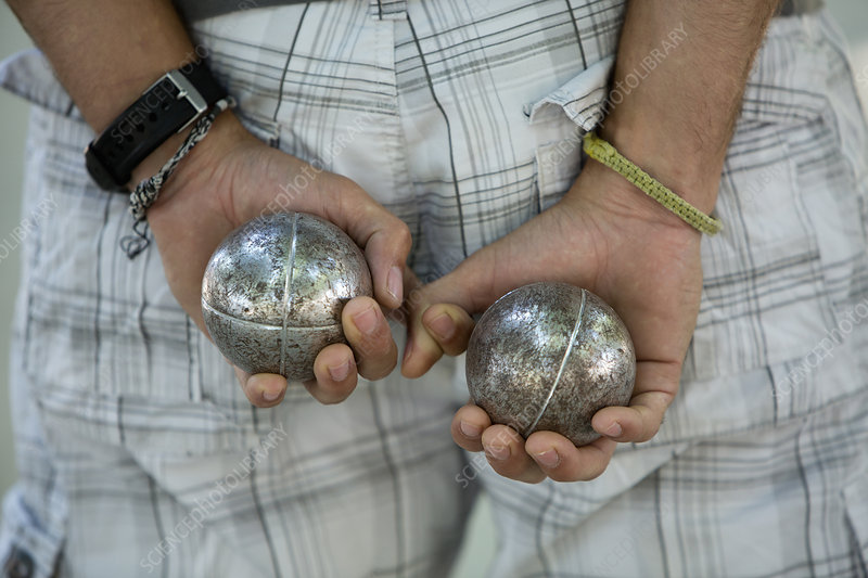 A boules player with a ball in each hand