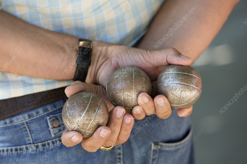 A boules player holding three boules