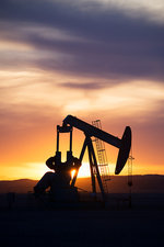 A pumpjack at a site at sunset
