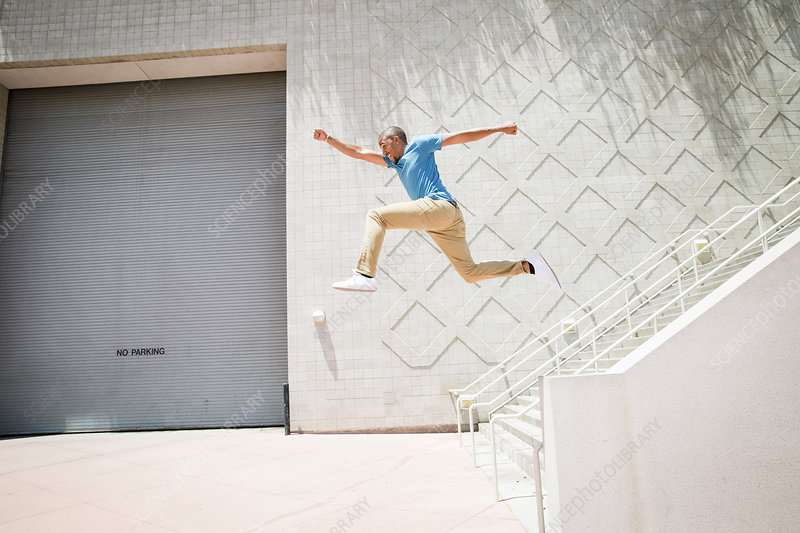 Young man jumping down a stairway