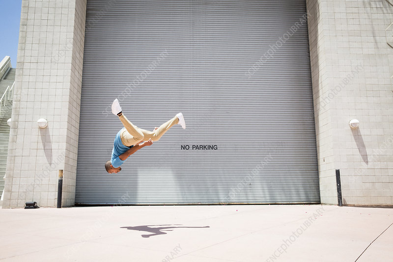 Young man somersaulting on a street