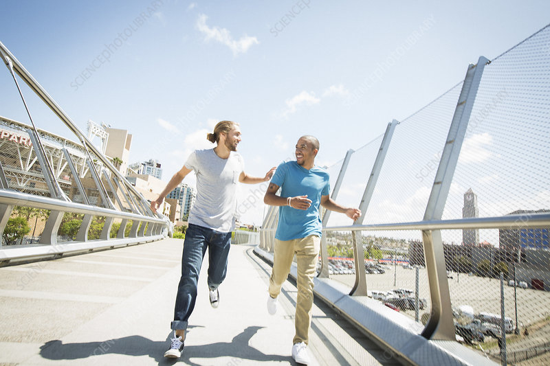 Two young men jogging along a bridge