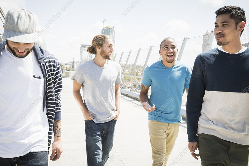 Group of young men walking along bridge